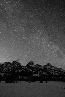 The starry night sky seen above Grand Teton, with a faint hint of the Milky Way.