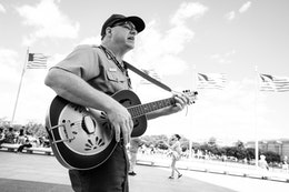 A Park Ranger playing the guitar and singing at the Washington Monument.