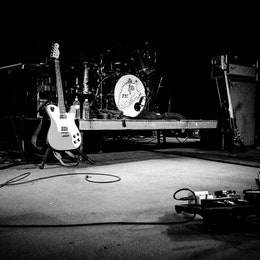 A couple guitars and a drumset on an empty stage ready for a Frightened Rabbit concert.