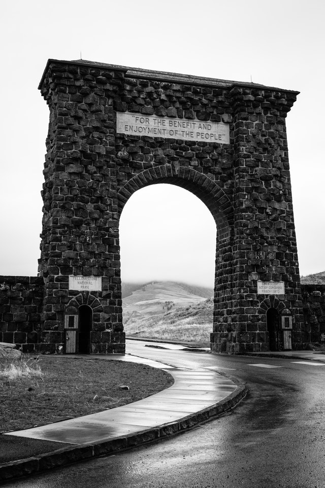 """The Roosevelt Arch at Yellowstone National Park on a foggy, rainy morning. The inscription at the top reads """"for the benefit and enjoyment of the people""""."""