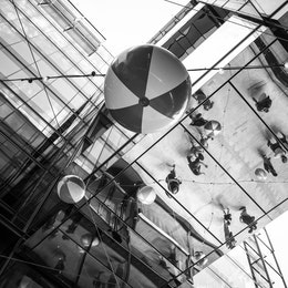 Beachballs hanging at CityCenterDC, with people reflected off the shiny ceiling.